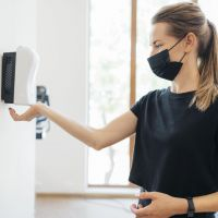 side-view-woman-with-medical-mask-disinfecting-her-hands-gym